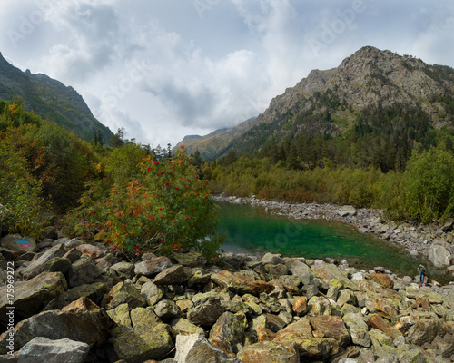 Fotobehang Bergrivier green Alpine lake surrounded by mountains in the autumn among the plants and bushes