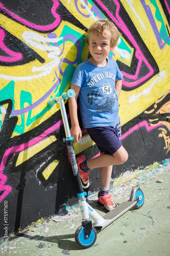 Young boy skateboarding with graffity