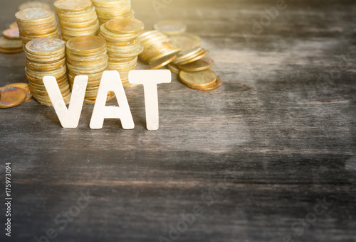 VAT wood word with stacked coins on dark wooden background