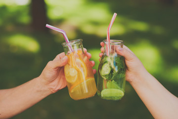 Friends celebrate with detox juice cocktailss on green nature background witn free space. Diet on the go, well being and weight loss, superfoods, health, vegetarian food concept