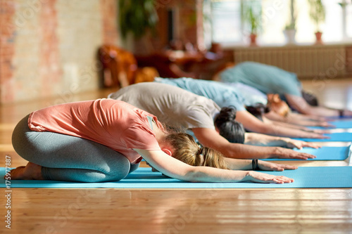 Sticker group of people doing yoga exercises at studio