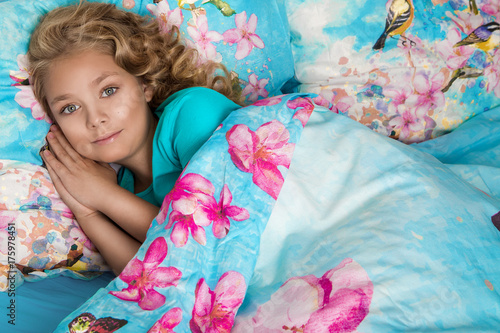 Foto op Aluminium Kasteel Gracious young beautiful blond girl, little princess with long hair and blue eyes, the child lies in bed, sleeps in a beautiful bedding flowers and butterflies