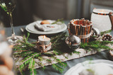 Festive Christmas and New Year table setting in scandinavian style with rustic handmade details in natural and white tones. Dining place decorated with pine cones, branches and candles - 175985636