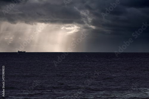 Ship on the horizon against sky with sunbeams