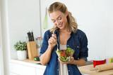 Beautiful young woman eating salad at home. - 175993090
