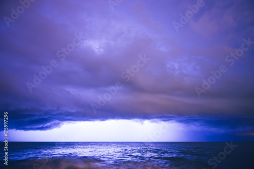 Foto op Canvas Violet Landscape of Thunderstorm at Night over the Surface of the Water with Clouds and Lightning