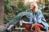 Joyful young woman having rest in camping - 176002228