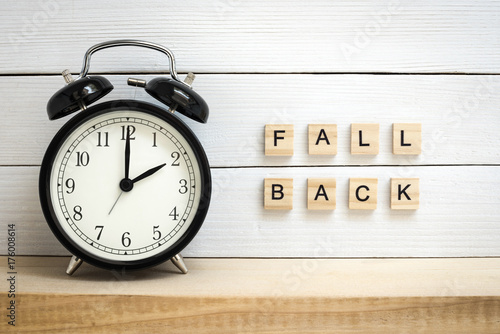 Daylight Saving Time Concept Represented with a Vintage Alarm Clock and Wooden Letters - 176008614