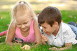 Cute little children with magnifying glasses lying on green grass in park