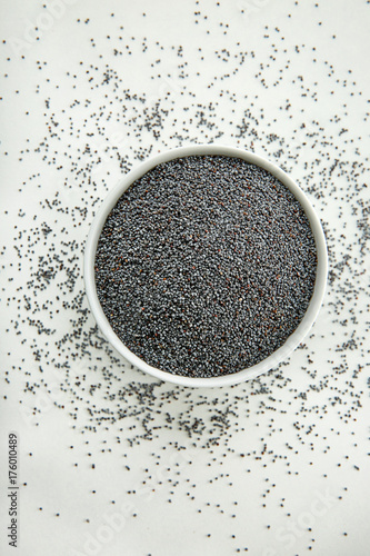 Bowl with poppy seeds on white background