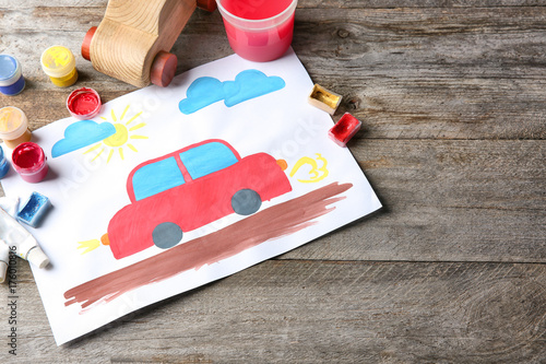 Child's painting of red car on table