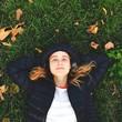 ragazza sdraiata sull'erba guarda il cielo - 176013005