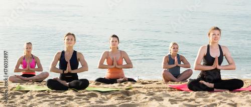 Fototapeta Glad women making yoga meditation in lotus pose