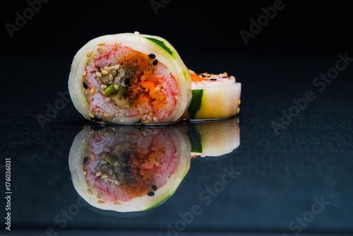 Foto op Canvas Sushi bar Sushi roll on dark reflective background