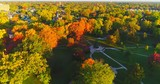 Looking down on breathtaking Autumn colors over park and neighborhood, aerial flyover. - 176038002