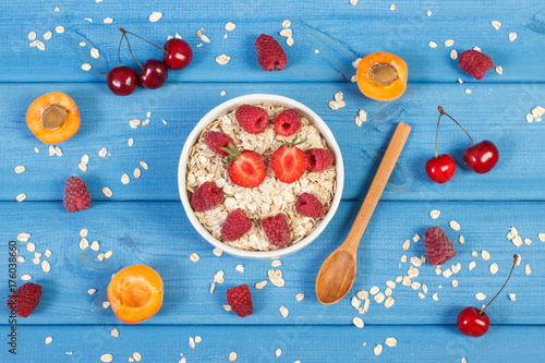 Wall mural Oatmeal with fruits and oat flakes, healthy lifestyle and nutrition concept
