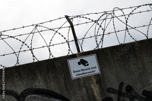 Mauer mit Stacheldraht videoüberwacht Poster
