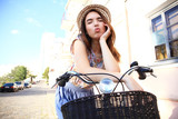 Charming woman on bike in city, during summer - 176049420