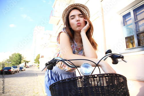 Naklejka Charming woman on bike in city, during summer