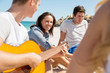 Beautiful young people with guitar on beach - 176052407