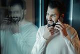 Attentive brunette touching his beard - 176054483