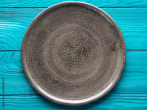 Gray ceramic textured plate dish background. Green wooden table