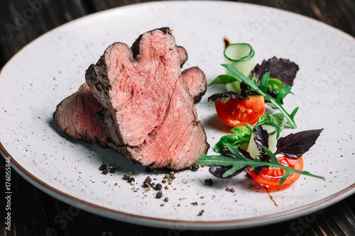 Foto op Aluminium Steakhouse Grilled beef steak with salad on dark wooden background