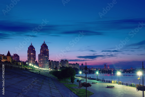 Foto op Canvas Kiev Embankment of modern european city with night illumination and colorful sky. Evening at the Dnieper river in Obolon, Kiev