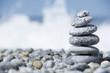 Stones pyramid on pebble beach symbolizing stability, zen, harmony, balance, concept with blur sea background - 176069445