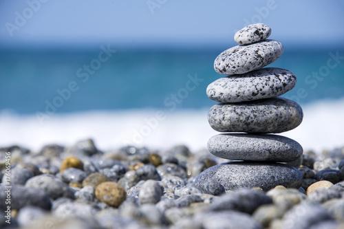 Foto op Canvas Zen Stones pyramid on pebble beach symbolizing stability, zen, harmony, balance, concept with blur sea background