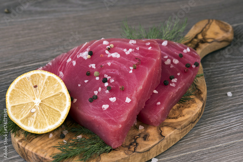 Poster Steakhouse Raw tuna fillet with dill, lemon and peppers in olive cutting board