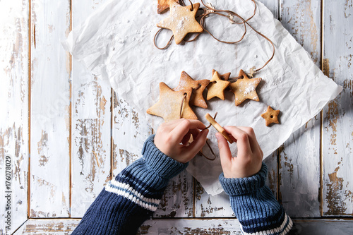 Child hands make garland of homemade shortbread star shape sugar cookies different size on thread on baking paper over white wooden plank table Poster