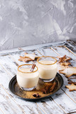 Eggnog Christmas milk cocktail with cinnamon, served in two glasses on vintage tray with shortbread star shape sugar cookies different size over white wooden plank table. - 176078225