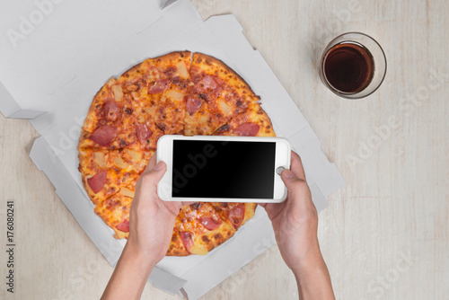 Man holding smartphone and tasty pizza with ingredients on wooden table Poster