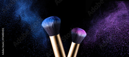 Makeup brush with pink and blue powder explosion isolated on black background - 176083455