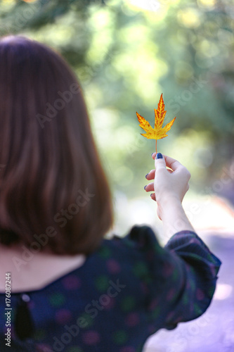 Tuinposter Purper girl holds a yellow leaf