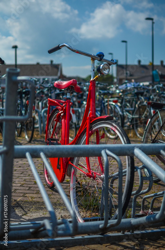 Staande foto Fiets red bike in a bicycle parking rack