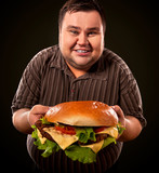 Man eating fast food hamberger. Fat person made great huge hamburger and admires him, intending to eat it. Junk meal leads to obesity. Person regularly overeats concept. Caricature of a fat man. - 176101269