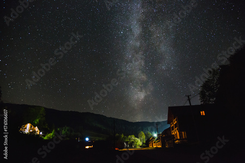 Fotobehang Zomer The Milky Way over the mountains and the village on a summer night.
