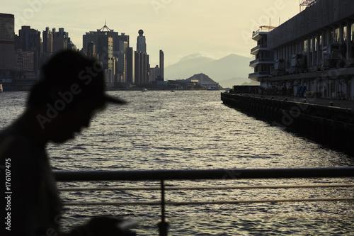 Sonnenuntergang in Hongkong mit Silhouette Mann am Handy Poster