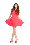 Smiling Woman In Pink Mini Dress Is Standing With Legs Crossed - 176108209