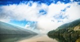 River amidst mountains against cloudy sky