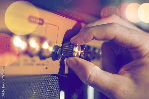 Fototapeta Detalle de mano de musico y amplificador.Ingenieria de sonido y produccion musical.