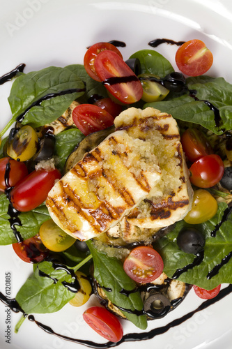 Poster Cyprus Grilled Halloumi Cheese poured with garlic olive oil salad witch grilled eggplant, cherry tomatoes, black olives and spinach. healthy food. Close up