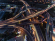 Vertical top down aerial view of traffic on freeway interchange at night.