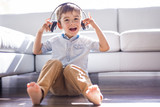 Happy little girl listening music close to the sofa living-room - 176127087