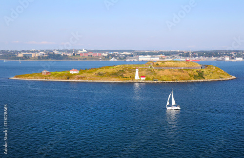 Aluminium Canada Lighthouse on Georges Island National Historic Site, with a sailboat in the Halifax Harbor on a bright sunny day in September in Halifax, Nova Scotia