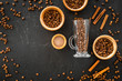 Quadro Ingredients for coffee. Roasted coffee beans and cinnamon on black background top view copyspace