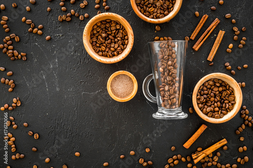 Wall mural Ingredients for coffee. Roasted coffee beans and cinnamon on black background top view copyspace