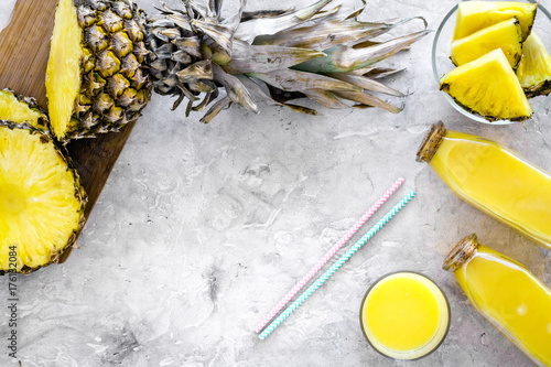 Staande foto Sap Non-alcoholic beverages. Bottle with fruit juice near pineapples slices on grey background top view copyspace